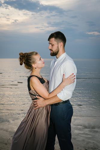 Romantisks pāris saulrietā pie jūras skatās viens otram acīs