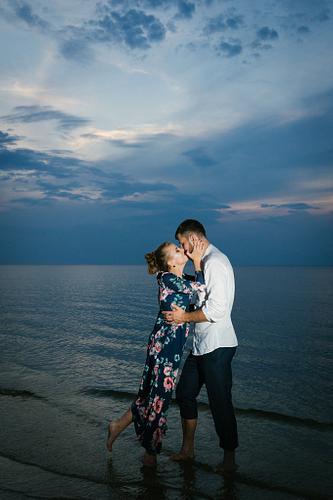 Pāris skūpstās stāvēdami jūrā ūdenī saulrieta fotosesijā