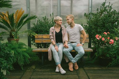Pāris sēž uz soliņa sadevušies rokās skatās viens otram acīs pāra fotosesija Botāniskajā dārzā