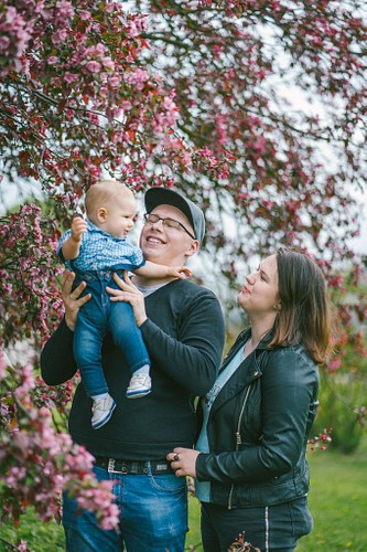 Jaunā ģimene ar mazuli pavasarī pie ziedošas ābeles