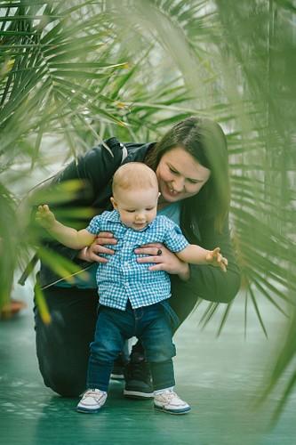 Mamma palīdz spert pirmos soļus, fotosesija zem palmu zariem botāniskajā dārzā