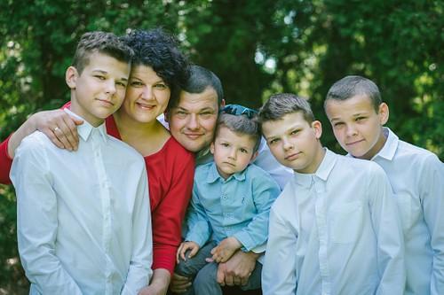 Ģimenes portrets vecāki kopā ar dēliem smaida