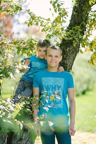 Mazākais brālis sēž kokā, apķēries ap kaklu lielajam brālim