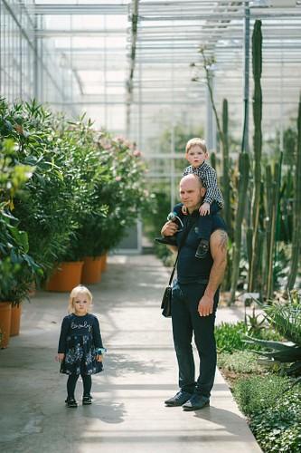 Ģimenes pastaiga ekskursija Botāniskajā dārzā Salaspilī, dēls sēž tētim uz pleciem