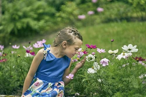 Meitene zilā kleitā osta ziedus