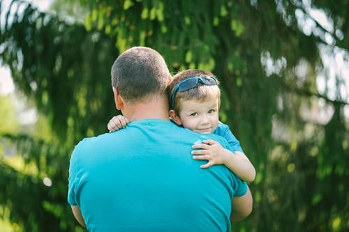 Dēls apķēries tētim ap kaklu, skatās pār plecu