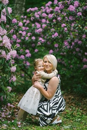 Meitenīte apskauj mammu ap kaklu uz rododendru fona Rīgā