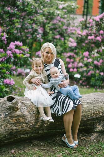 Mamma ar bērniem sēž rododendru parkā uz nozāģēta koka