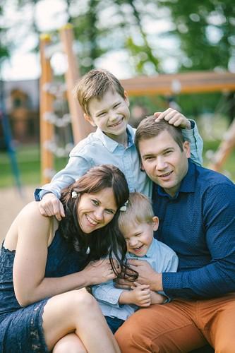 Vecāki ar bērniem sēž uz soliņa bērnu rotaļu parkā, kutina brāli un smejas
