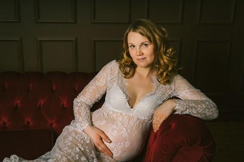 Topošā māmiņa caurspīdīgā mežģīņu kleitā fotosesijā studijā uz sarkana samta dīvāna
