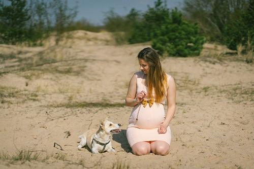 Grūtniece un suns kāpās pie jūras sēž smiltīs
