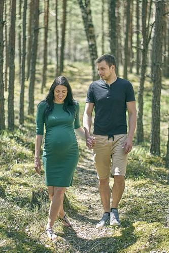 Grūtniece zaļā kleitā priežu mežā kopā ar topošo tēti