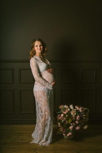 Gaidību foto baltā mežģīņu kleitā studijā ar tumšu fonu un ziedu pušķi