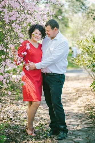 Romantiska fotosesija ziedošā pavasarī sieviete sarkanā kleitā vīrietis uzvalkā