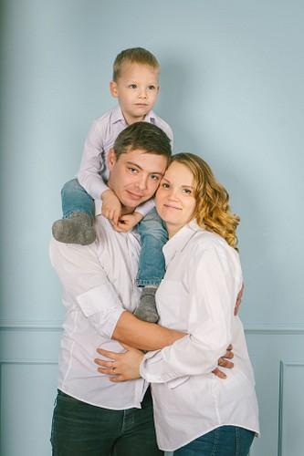ģimene baltos kreklos fotostudijā uz zila fona gaidot ģimenes pieaugumu