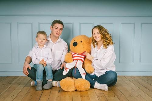 ģimenes fotosesija studijā rīgā saskaņoti baltos tērpos sēž uz dēļu grīdas ar lielu lāci
