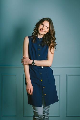 sieviete zilā kleitā pie zilas sienas fotostudijā