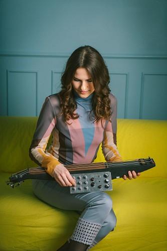 mūziķes fotosesija studijā ar instrumentu rokās