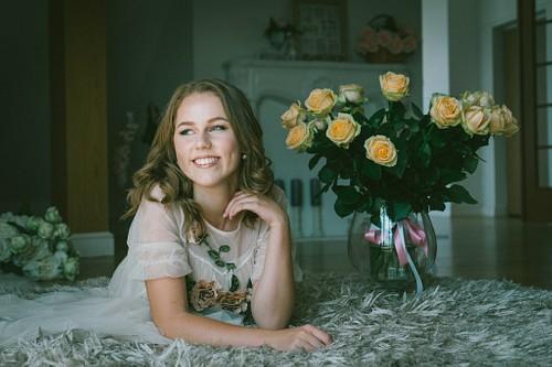meitene ar rozēm guļ uz bieza balta paklāja fotostudijā