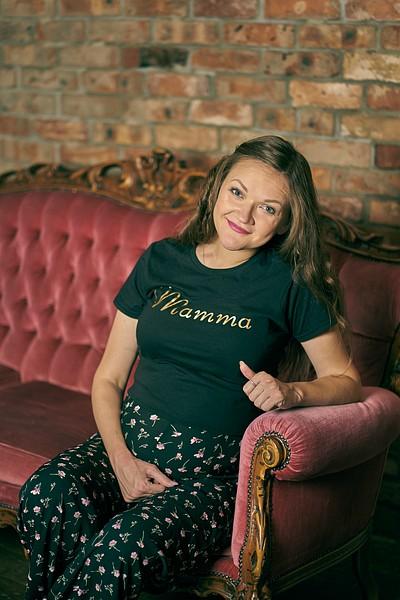 Gaidības puncis fotosesijā melna t-kreklā mamma sēž uz karaliska sarkana dīvāna studijā
