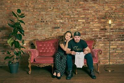 Topošie vecāki sēž sarkanā veclaicīgā dīvānā pie ķieģeļu sienas tētis tur rokās mazuļa bodiju ar uzrakstu