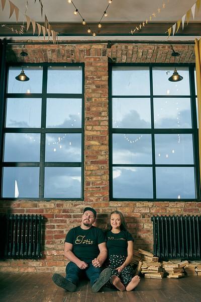 Jautri un romantiski pāris sēž uz grīdas starp melniem radiatoriem uz zem lieliem logiem sadevušies rokās pie griestiem lampiņas un karodziņi