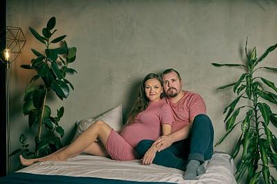 Fotosesija mājas vidē topošie vecāki sēž gultā saskanīgi saģērbušies pelēka apmetuma siena lielas puķes guļamistabā