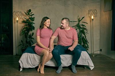 Romantisks pāris sēž uz gultas malas un skatās viens uz otru sadevušies rokās sarkanā kleitā un kreklā fonā pelēka apmetuma siena un stilīgas stāvlampas studijā lifestyle tipa fotosesija