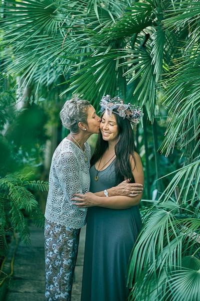 Māte un meita Oranžērijā Botāniskajā dārzā starp palmu lapām, buča uz vaiga, pērļu kronis galvā