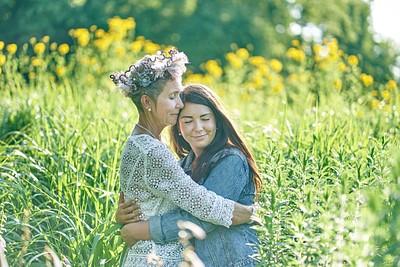Māte un meita apskāvušās saulainā vasaras dienā pie cilvēka auguma garām puķēm