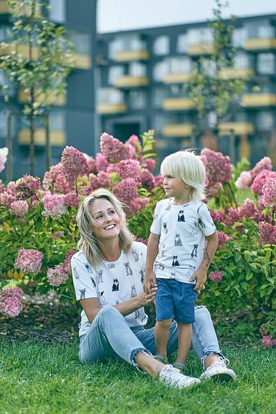 Mamma ar dēlu sēž zālē pie rozā hortenziju krūma daudzīvokļu mājas pagalmā pilsētvidē