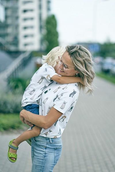 Mamma nes savu dēlu uz rokām, puika apķēries mammai ap kaklu, saskaņoti t-krekli fotosesijai