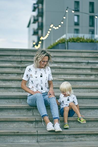 Mamma un dēls sēž uz kāpnēm pilsētā fonā kafejnīcas lampiņu virtenes