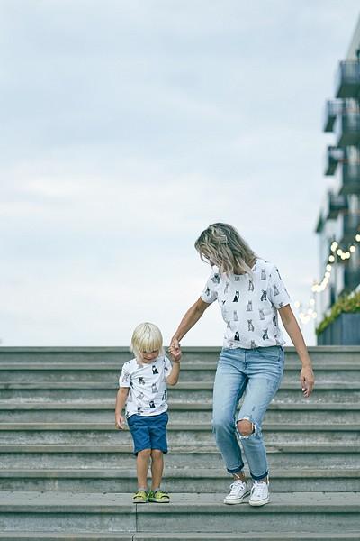 Mamma un dēliņš lēkā pa kāpnēm uz leju saskaņotos t-kreklos pilsētvidē fotosesija