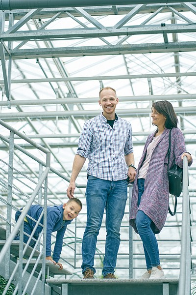 Vecāki un dēls muļķojas četrāpus smejas Botāniskā dārza iekštelpās uz kāpnēm