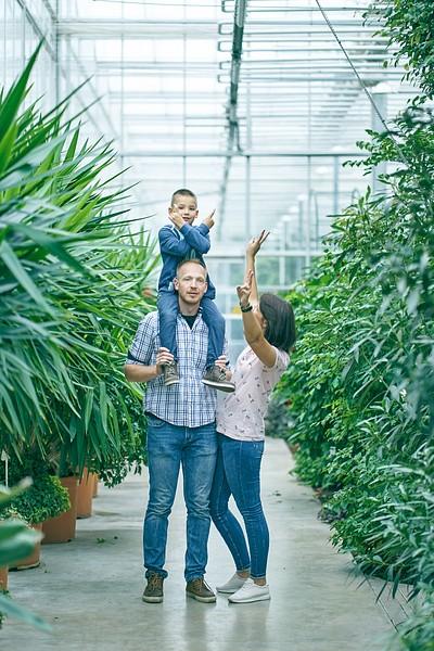 Dēls sēž tētim uz pleciem mamma māj ar roku un smejas Oranžērijā uz celiņa starp lieliem tropiskiem augiem