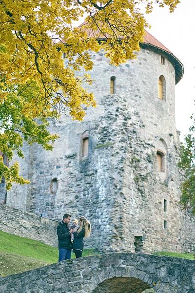 Jaunā ģimene ar mazuli stāv uz akmens tiltiņa fonā Cēsu pils tornis rudens koši dzeltenas lapas Cēsīs
