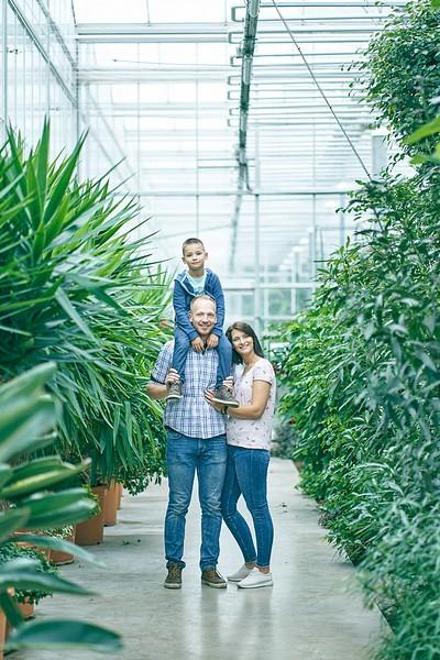 Puika sēž tētim uz pleciem mamma stāv blakus un smaida Oranžērijā starp tropiskajiem augiem