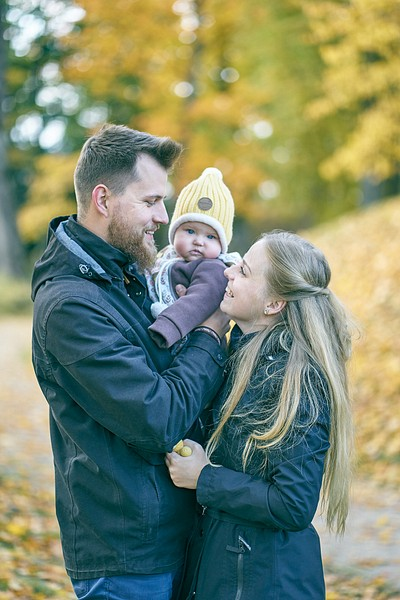 Jaunā ģimene ar mazuli laimīgi smejas rudenīgās koši dzeltenās krāsās melnās virsdrēbeēs