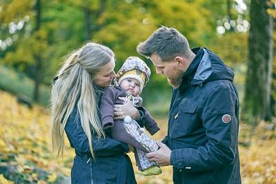 Mazulis rokās starp vecākiem abi skatās uz mazo zelta rudens Cēsu parkā