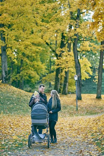 Zelta rudens Cēsīs ģimene ar ratiņiem un mazuli tēta rokās pastaigās pa parka celiņiem