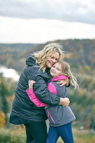 Mamma apskauj meitu stāvot uz kalna Siguldas Svētku laukumā fonā rudens krāsotie meži un Gauja