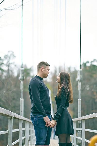 Pāris stāv uz Gājēju tiltu pār Gauju Krimuldā sadevušies rokās skatās viens otram acīs