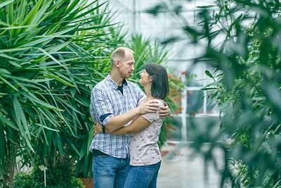 Pāris apskāvies skatās viens otram acīs Botāniskā dārza Oranžērijā starp tropiskiem augiem
