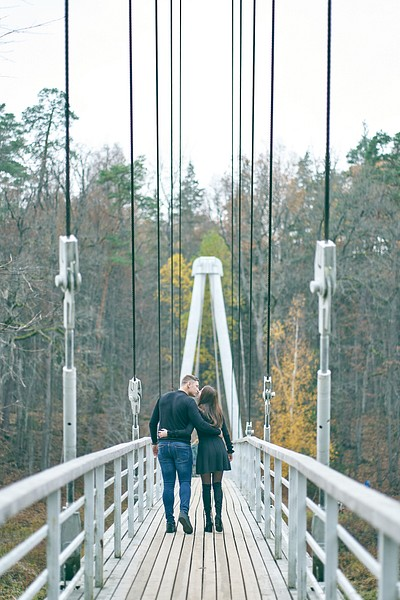 Pāris sadevušies rokās iet pār tiltu pār Gauju Krimuldā šaurs vanšu tilts