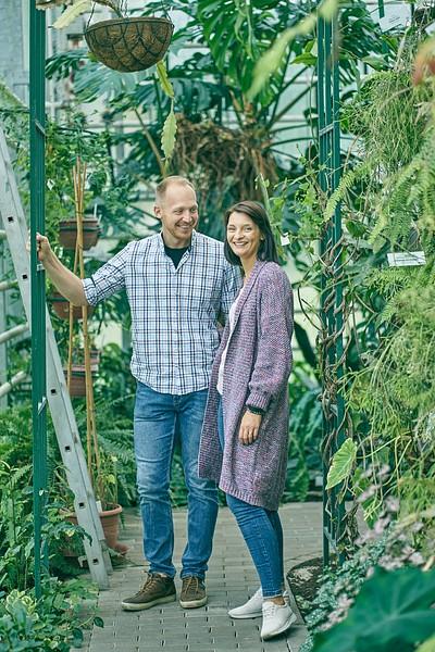 Pāris Botāniskajā dārzā pozē starp augiem vīrietis pieturas pie trepēm
