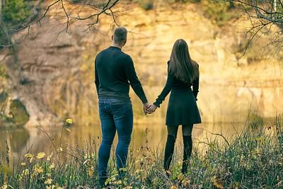 Zelta rudenis Siguldā pāris stāv rokās sadevušies un skatās pār Gauju uz zeltainas krāsas Velnalas klinti