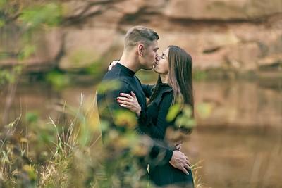 Pāris melnās drēbēs apķērušies skūpstās uz Velnalas zeltainās krāsas klints