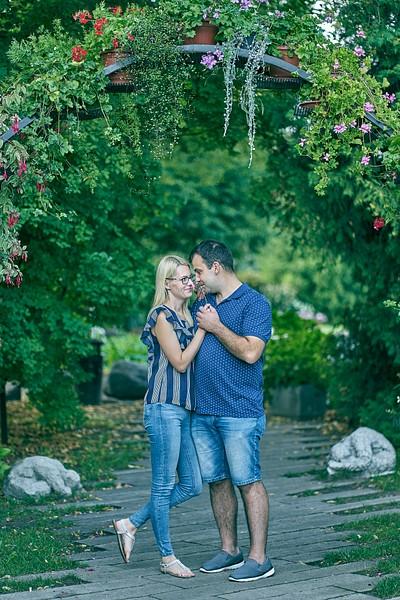Pāris apķērušies zem dekoratīva ziediem rotāta ieloka smaržo puķi ko vīrietis tur rokās