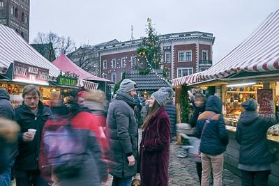 Pāris stāv un skatās viens otram acīs apkārt izplūdis pūlis svētku tirdziņš Ziemassvētkos